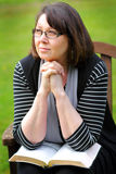 Prayer Warrior. A dark haired senior citizen lady sitting peacefully gazing and daydreaming with a bible and folded hands. Shallow depth of field Stock Photo