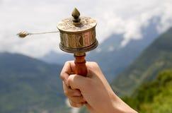 Prayer wheel. Girl holding prayer wheel  on the background of mountains in Tibet Royalty Free Stock Image