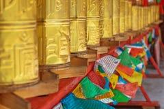 Prayer wheel. Tibetan golden prayer wheel with prayer flags Stock Photo