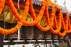 Prayer wheel and garlands of flowers Royalty Free Stock Image