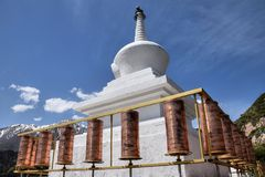Prayer wheels and a small white pagoda near the Mati Temple in Gansu province in China. Prayer wheels are a cylindrical wheels on a spindle made from metal stock image