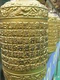 Prayer wheels. Golden prayer wheels in a Buddhist temple,worn hands Stock Images