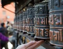 Prayer wheels and hand. View of Prayer wheels and hand Stock Photography
