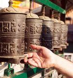Prayer wheels and a hand. View of Prayer wheels and a hand Royalty Free Stock Photos