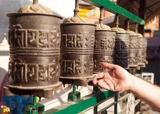 Prayer wheels and a hand. View of prayer wheels and a hand Stock Photo