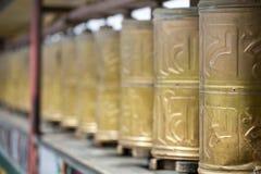 Prayer wheels in in Lhasa Monastery. Yellow Gold Prayer wheels in in Lhasa Monastery in Tibet Royalty Free Stock Photo