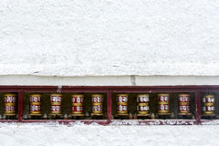 Prayer wheels on white wall. Of monastery in the north of India stock photos