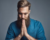 Prayerful bearded young man with palms together Royalty Free Stock Images