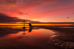 Prayerful Man. Man praying at a cross on a beach with a wonderful sunset sky behind him Royalty Free Stock Photos