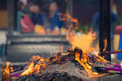 Prayers burning incense sticks in fire Royalty Free Stock Photo