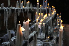 Prayers of the Faithful. Candles lighted by Pilgrims in front of a shrine, representing prayers intentions of the Faithful Royalty Free Stock Photography