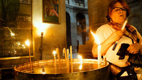Prayers lighting candles in Holy Sepulcher Church Royalty Free Stock Photography