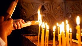 Prayers lighting candles in Holy Sepulcher Church Stock Photos
