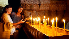 Prayers lighting candles in Holy Sepulcher Church Stock Images