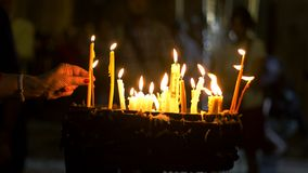 Close up of prayers hands lighting candles in the Holy Sepulchre Church in Jerusalem stock photo