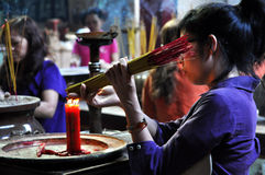 Prayers in a pagoda. Vietnam. SAIGON - FEB 18: Unidentified people offering incense sticks for the Gods in the Vietnamese Jade Emperor Pagoda. On February 18 Royalty Free Stock Photo