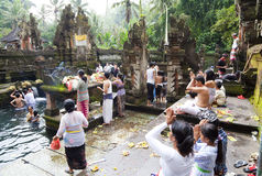 Prayers at Tirtha Empul, Bali, Indonesia. Image of devotees offering prayers and going through a hindu ritual at a religious bathing pool located within a temple royalty free stock photography