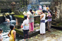 Prayers at Tirtha Empul, Bali, Indonesia. Image of devotees offering prayers and going through a hindu ritual at a religious bathing pool located within a temple stock photo