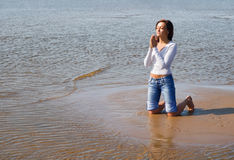 Praying-3. Girl praying on a beach Stock Photography