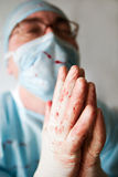 Praying. Surgeon, bespattered with blood, praying for patient life. Low DOF, focal point is on hands Royalty Free Stock Photo