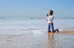 Praying-4. Girl praying on a beach Royalty Free Stock Photo