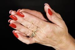 Praying. Mature woman with long red fingernails praying stock image