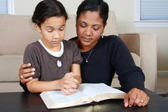 Praying. Minority woman and her daughter praying together Stock Images
