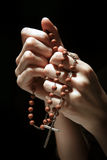 Praying. In the dark with a rosary Royalty Free Stock Image