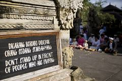 Praying. Sign stating don't stand in front of people who are praying in a Balinese temple in Ubud, Bali, Indonesia Royalty Free Stock Photos