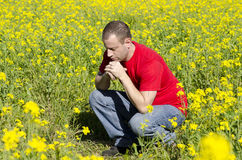 Praying alone in a field of yellow flowers. Stock Photos