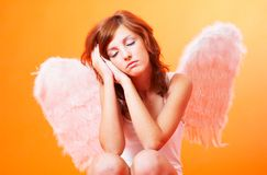 Praying Angel. An angel praying with her head leaning against her hands and her eyes closed Royalty Free Stock Image