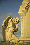 Praying angel. Angel sculpture praying in front of stone tomb, yellow dusk sun Stock Images