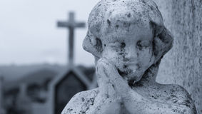Praying Angel. A praying angel at a cemetery with a cross kin the background Stock Photos