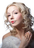 Praying angel. Studio portrait of beautiful young blond female model angel with curly hair, hazel eyes, wearing tender light makeup with red lips, top with Stock Photo