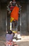 Praying at Angkor. A woman prays to a budhist statue clad in orange at Angkor Wat, Cambodia Stock Photography
