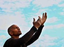 Praying with arms outstretched Stock Photo