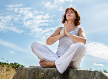 Praying beautiful middle aged woman in yoga position over blue sky. Exercising outdoors - praying beautiful middle aged woman sitting on a stone in yoga position Stock Images