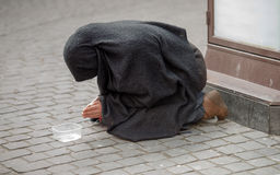 Praying and begging woman kneeling on the street Stock Images