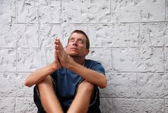 Praying for Better Times. A young man sitting on a city sidewalk, his hands in a praying position and looking upwards Royalty Free Stock Images