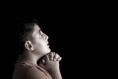 Praying boy. Low key portrait of a boy  praying in the dark Royalty Free Stock Photos
