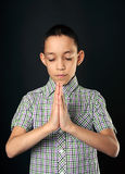Praying boy closed eyes over black Stock Photo