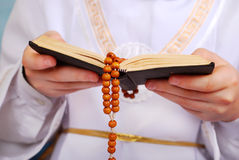 Praying boy going to the first holy communion. Hands of praying boy going to the first holy communion holding prayer book and wooden rosary Stock Images