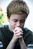 Praying boy. Praying teenager boy with folded hands Royalty Free Stock Photos