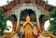 Praying Buddha statue standing at entrance of ancient Buddhist temple structure, Thailand Stock Photos