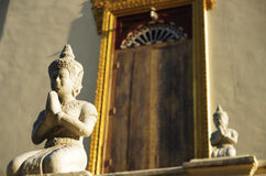 Praying buddha statue at a temple. Two Buddha sculptures in front of a buddhist temple in Asia, golden door framing behind Royalty Free Stock Photo