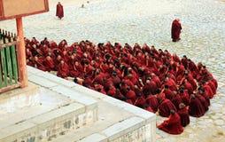 Praying buddhist monks. Xiahe, Gannan Tibetan Autonomous Prefecture, China - October 3, 2013: a group of Tibetan monks praying on the courtyard of Labrang Stock Photography
