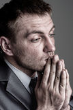 Praying businessman. Portrait of sad praying businessman looking for solutions stock photos