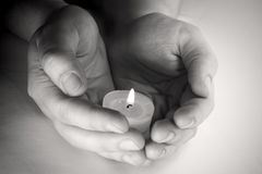 Praying candle. Hands holding praying candle.Black and white image. rn Royalty Free Stock Photography