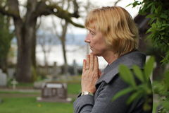Praying in cemetery for loved ones Stock Images