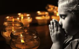 Praying child with candles. Royalty Free Stock Photo